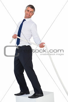 Smiling businessman standing on a cube and pulling rope