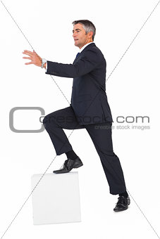 Businessman climbing on a cube with arms out