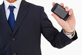 Mid section of a businessman holding smartphone