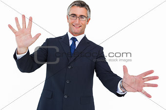 Smiling businessman in glasses with arms out