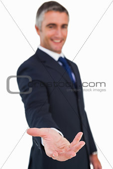Smiling businessman in suit with arm out