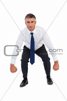 Businessman bending and clenching fists