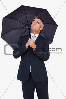 Smiling businessman sheltering with umbrella