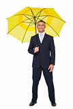 Smiling businessman under yellow umbrella