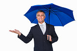 Happy businessman under umbrella with hand out