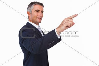 Smiling businessman in suit pointing