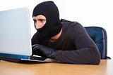 Burglar with balaclava hacking a laptop