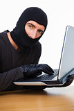 Burglar typing on laptop and looking at camera