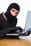 Burglar typing on laptop and looking at camera