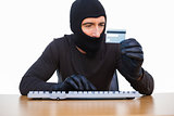 Burglar typing on keyboard and holding credit card