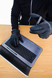 Mid section of a burglar using laptop and smartphone