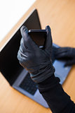 Hands with leather gloves using laptop and smartphone