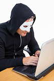 Burglar with white mask hacking a laptop