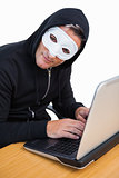 Hacker with white mask using laptop and looking at camera