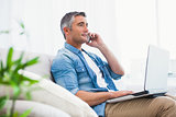Cheerful man sitting on couch phoning and using laptop