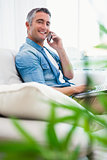 Happy man sitting on couch phoning and using laptop