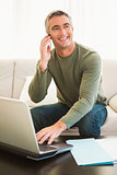 Happy man on the phone using laptop