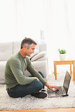 Smiling man sitting on carpet using laptop