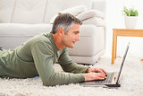 Smiling man lying on carpet using laptop