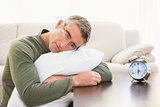 Man resting on cushion with alarm clock on the table