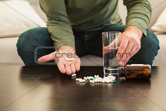 Casual man showing pills on open hand