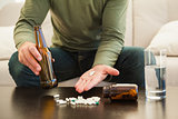 Man showing pills and holding beer bottle