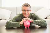 Smiling man with a pink piggy bank
