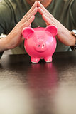 Mid section of a man with joined hands on piggy bank