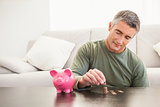 Smiling man putting some coins into a piggy bank