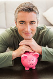 Smiling casual man resting head on piggy bank