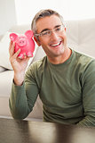 Smiling man posing with a piggy bank