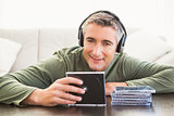 Smiling man listening music and holding cd