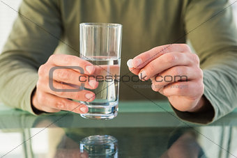Close up of man holding a pill and glass of water