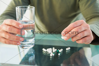 Close up of a man holding pill and glass of water