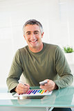 Smiling man analyzing chart and holding mobile phone