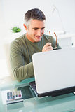 Smiling man holding glasses and using laptop