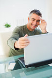 Cheerful man sitting and holding his laptop