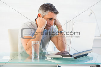 Tired man sitting and looking his laptop