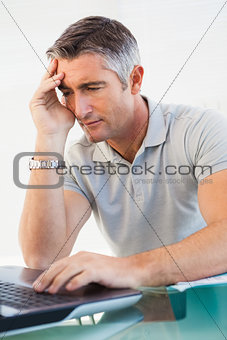 Tired man sitting and using his laptop
