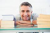 Happy man posing between books