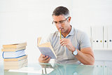 Man with glasses thinking and reading a book