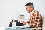 Retro man with cigarette typing on typewriter