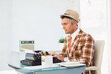 Retro man in straw hat typing on typewriter