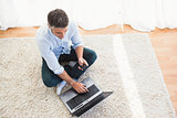 Man sitting on carpet using laptop and phone