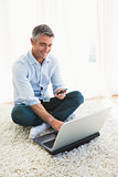 Happy man sitting on carpet using laptop and phone