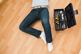 Man lying with a tools box near him