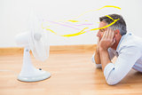 Man lying in front of an electronic fan with ribbons