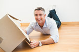 Happy man lying on floor with box looking at camera
