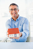 Happy man with glasses showing model house