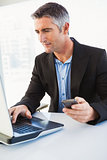 Businessman using laptop and holding smartphone